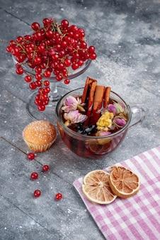 Vista frontal de cranberries vermelhas frescas com xícara de chá de canela na mesa de luz