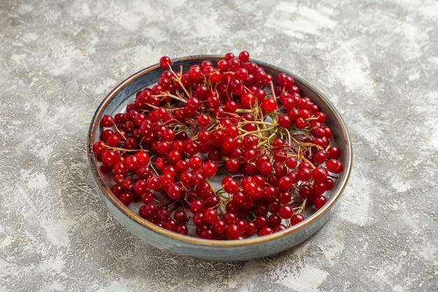 Vista frontal de cranberries vermelhas frescas dentro da bandeja na mesa branca baga cor de frutas vermelho selvagem