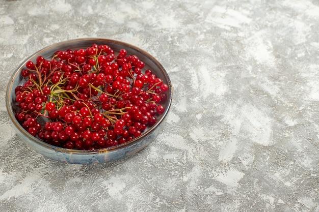 Vista frontal de cranberries vermelhas frescas dentro da bandeja na mesa branca clara com frutas vermelhas silvestres