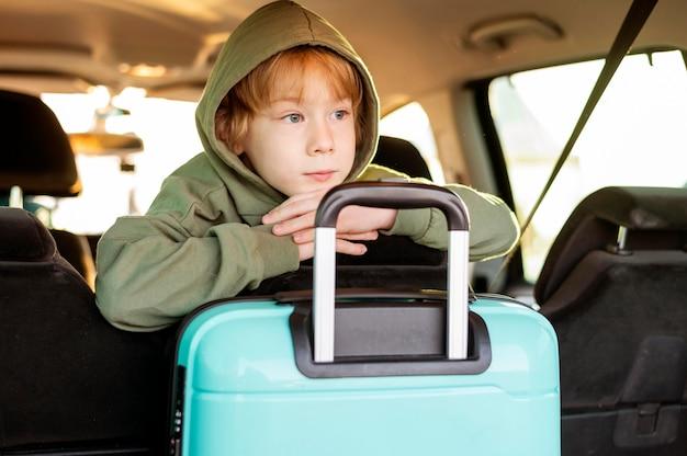 Vista frontal de criança com bagagem dentro do carro
