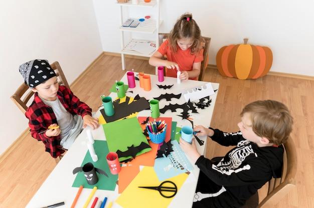 Vista frontal de crianças com arranjos do conceito de halloween