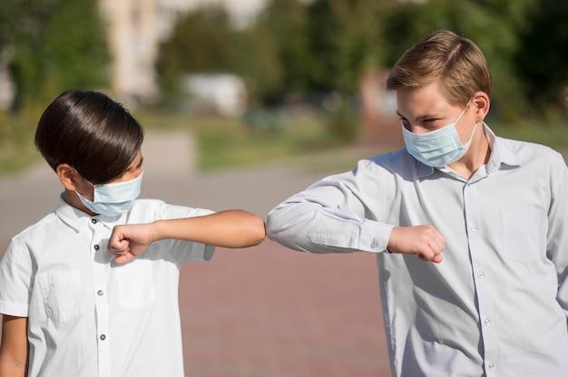 Vista frontal de crianças cumprimentando com cotoveladas