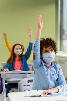 Vista frontal de crianças levantando as mãos na aula