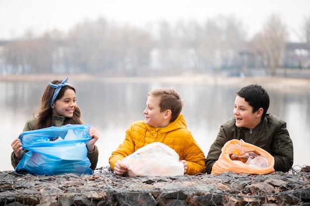 Vista frontal de crianças sorridentes com sacos de plástico