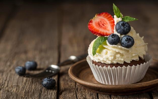Vista frontal de cupcake saboroso com morango e mirtilo