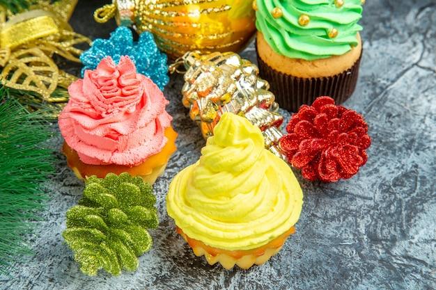 Vista frontal de cupcakes coloridos e enfeites de natal em cinza