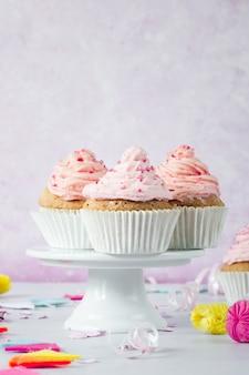 Vista frontal de cupcakes de aniversário com glacê e confeitos