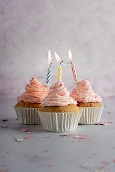 Vista frontal de cupcakes de aniversário com glacê e velas acesas