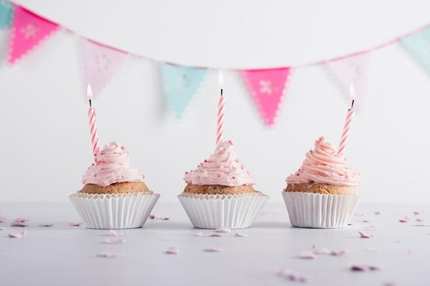 Vista frontal de cupcakes de aniversário com velas acesas e guirlanda