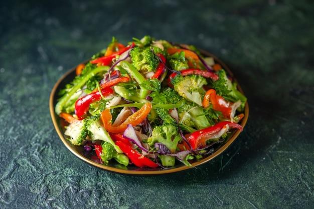 Vista frontal de deliciosa salada de vegetais com vários ingredientes em fundo escuro