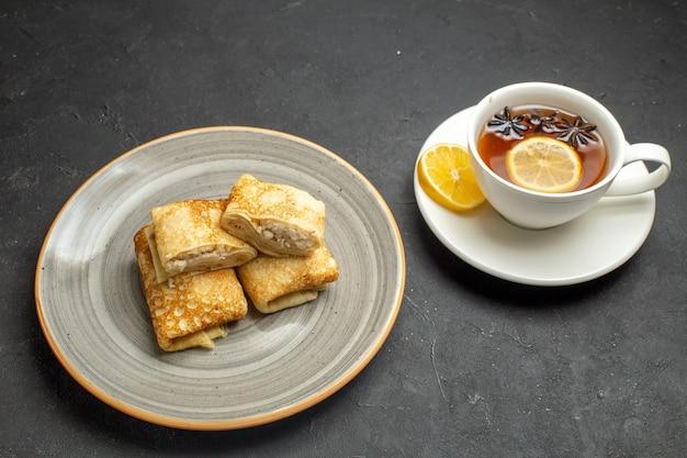 Vista frontal de deliciosas panquecas frescas em um prato branco e uma xícara de chá preto em fundo escuro