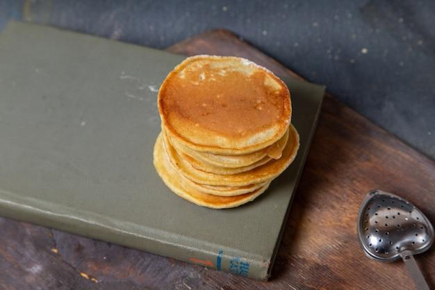 Vista frontal de deliciosas panquecas na mesa de madeira de caderno e superfície cinza