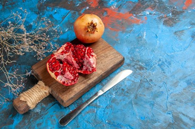 Vista frontal de deliciosas romãs na tábua de cortar faca de jantar em abstrato azul com espaço livre