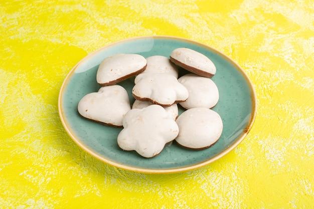Vista frontal de deliciosos biscoitos com recheio de chocolate dentro de uma placa verde na superfície amarela