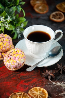 Vista frontal de deliciosos biscoitos de açúcar e uma xícara de café em um vaso de flores secas com rodelas de limão em um fundo escuro de cores misturadas