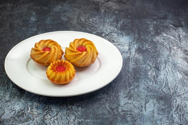 Vista frontal de deliciosos biscoitos em um prato branco na superfície escura