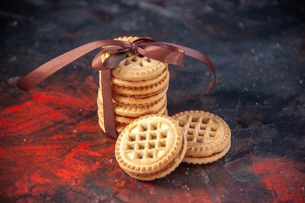 Vista frontal de deliciosos biscoitos empilhados no fundo da mistura de cores com espaço livre