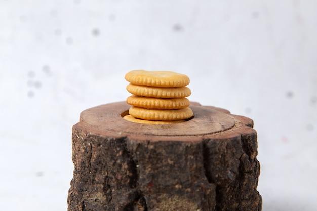 Vista frontal de deliciosos biscoitos redondo formado na mesa de madeira marrom e superfície whtie