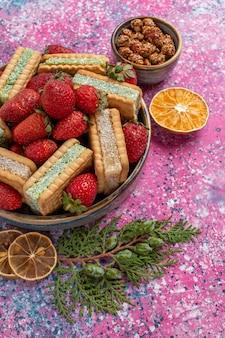 Vista frontal de deliciosos biscoitos waffle com morangos vermelhos frescos