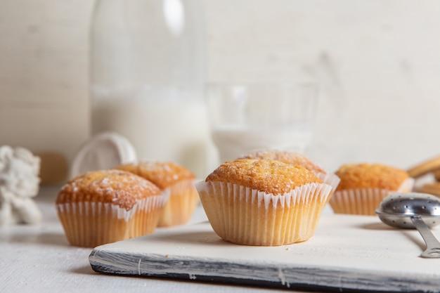 Vista frontal de deliciosos bolos com açúcar em pó na mesa branca