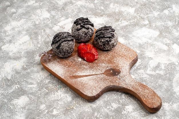 Vista frontal de deliciosos bolos de chocolate com morangos na superfície branca