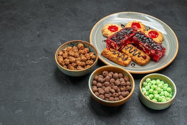 Vista frontal de deliciosos bolos de frutas com biscoitos e doces no espaço escuro