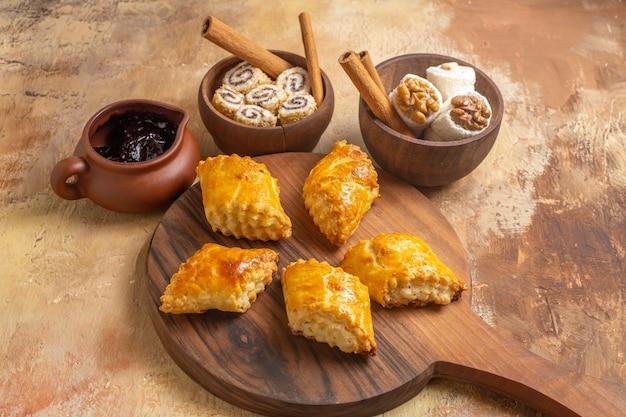 Vista frontal de deliciosos bolos de nozes com confitures na superfície de madeira