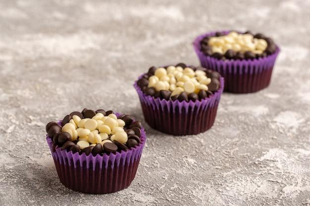 Vista frontal de deliciosos brownies de chocolate com pepitas de chocolate na superfície clara