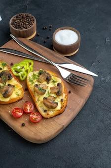Vista frontal de deliciosos petiscos com legumes frescos de cogumelos e talheres em temperos de tábua de madeira em fundo preto