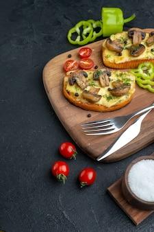 Vista frontal de deliciosos petiscos com legumes frescos de cogumelos e talheres em temperos de tábua de madeira no lado esquerdo em fundo preto