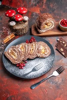 Vista frontal de deliciosos rolos de biscoito dentro do prato na superfície escura
