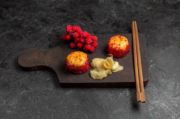 Vista frontal de deliciosos rolos de sushi de peixe com peixe e arroz, juntamente com gravetos na parede cinza