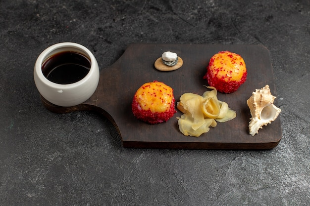 Vista frontal de deliciosos rolos de sushi de peixe com peixe e arroz junto com molho na parede cinza