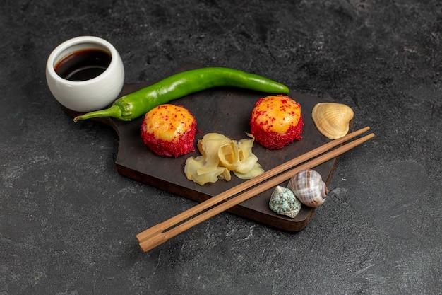 Vista frontal de deliciosos rolos de sushi de peixe com peixe e arroz junto com pimenta verde e palitos na parede cinza