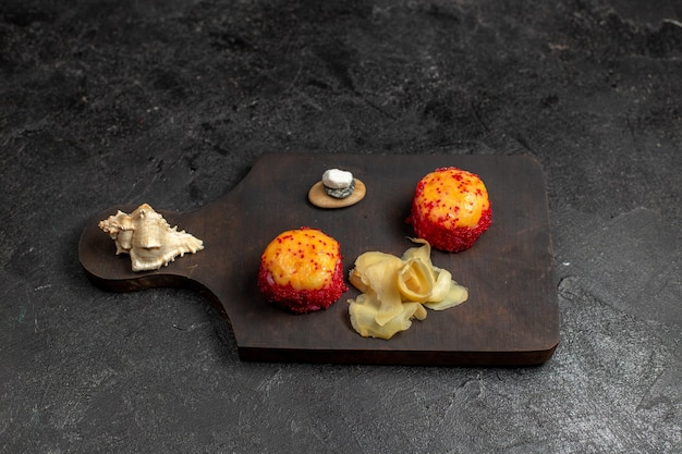 Vista frontal de deliciosos rolos de sushi de peixe com peixe e arroz na parede cinza