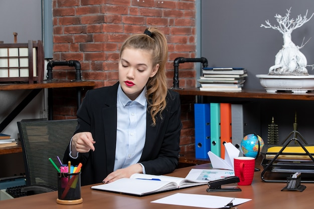 Vista frontal de determinada jovem sentada a uma mesa e apontando um ponto do documento no escritório