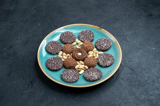 Vista frontal de diferentes biscoitos de chocolate com nozes em uma superfície cinza-escura