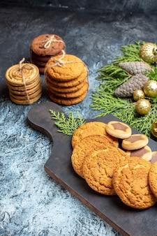 Vista frontal de diferentes biscoitos deliciosos em superfície claro-escuro