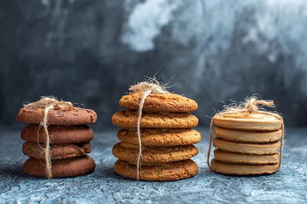 Vista frontal de diferentes biscoitos deliciosos no fundo claro