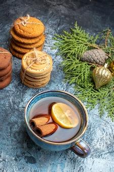 Vista frontal de diferentes biscoitos doces com uma xícara de chá no fundo claro