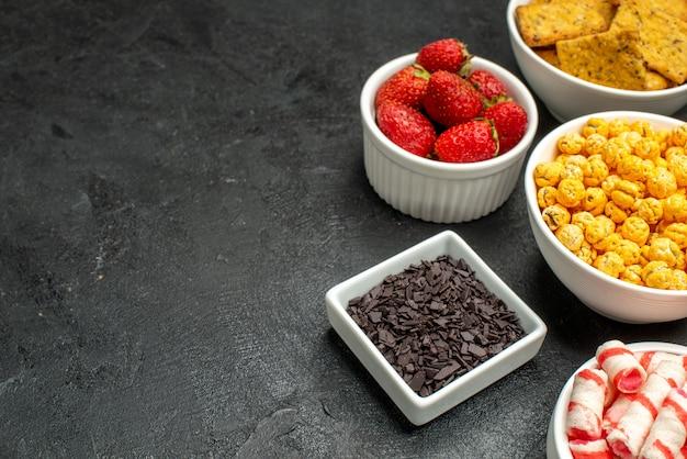 Vista frontal de diferentes comidas, biscoitos, frutas e doces