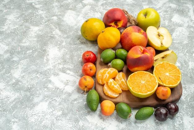 Vista frontal de diferentes composições de frutas fatiadas e frutas inteiras frescas no espaço em branco