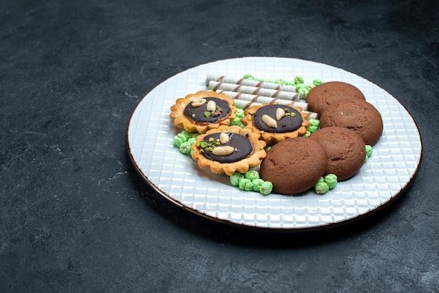Vista frontal de diferentes cookies de chocolate à base de doces de açúcar na superfície cinza