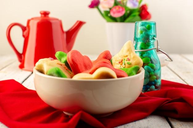Vista frontal de diferentes deliciosos biscoitos coloridos formados dentro da placa com chaleira vermelha e doces