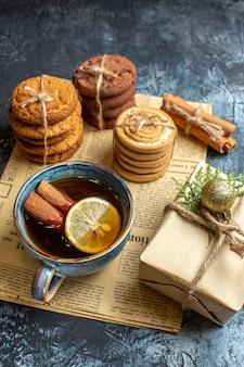 Vista frontal de diferentes deliciosos biscoitos com uma xícara de chá em um fundo claro