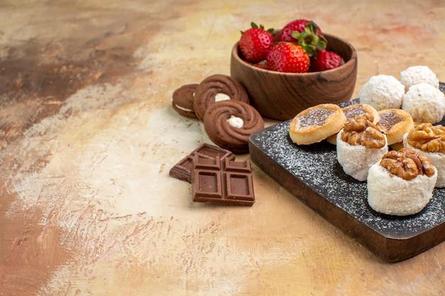 Vista frontal de diferentes doces com biscoitos e frutas em um bolo de torta de frutas de mesa leve