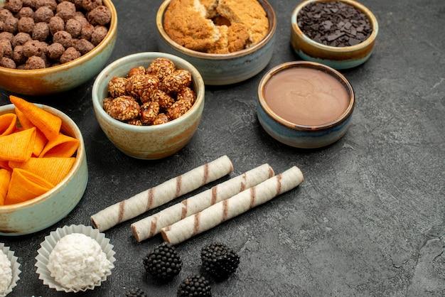 Vista frontal de diferentes ingredientes cips, flocos e nozes em fundo cinza refeição lanche cor café da manhã