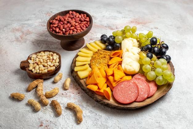 Vista frontal de diferentes lanches cips, salsichas, queijo e uvas frescas com nozes no espaço em branco
