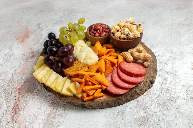 Vista frontal de diferentes lanches nozes cips, queijo e salsichas no fundo branco
