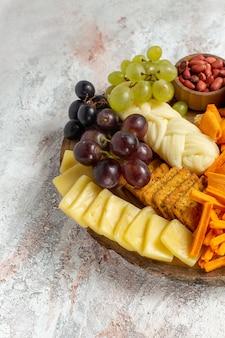 Vista frontal de diferentes lanches nozes cips uvas queijo e salsichas no fundo branco porca lanche refeição alimentos frutas